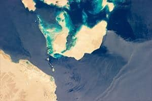 This photograph taken by an astronaut on the International Space Station (ISS) illustrates the morphology of the Strait.The relatively clear, deep-water passages of the western Strait of Tiran are visible at image left, while the more sinuous, shallow-water passage on the Saudi Arabia side can be seen at image top center. Credit: NASA/JSC, Expedition 36 Crew, ISS.